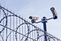 security-cameras-over-fence-mounted-steel-barbed-wire-30665401